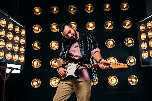 Chitarrista barbuto maschio in giacca di pelle nera sul palco con decorazioni di luci.