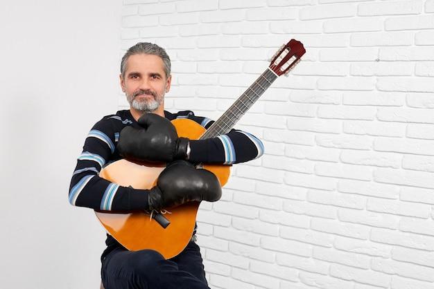 Chitarrista che indossa nella posa dei guantoni da pugile.