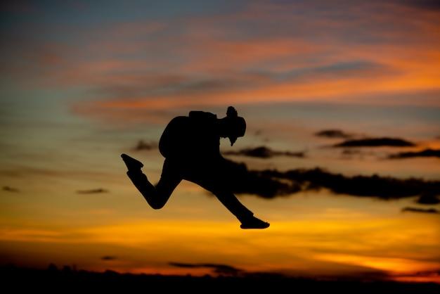 Chitarrista della ragazza della siluetta su un tramonto