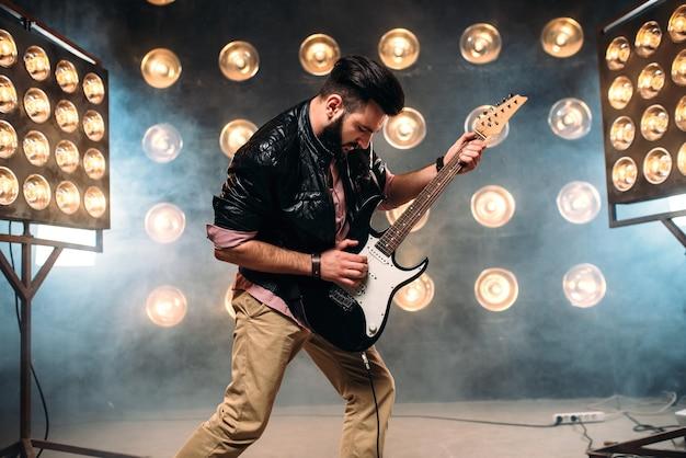 Chitarrista maschio sul palco con decorazioni di luci