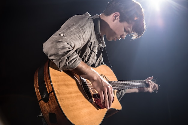 Chitarrista, musica. un giovane suona una chitarra acustica su uno sfondo nero isolato. luce puntata