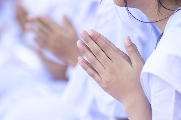 Chiuda fino alla mano della ragazza che fa pregare buddista.