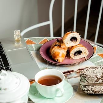 Chiuda fino alla tavola rotonda con il taccuino e la borsa della tazza_ del tè del croissant del cioccolato
