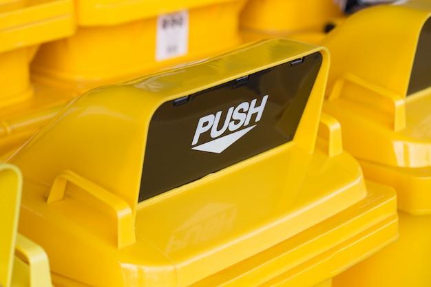 Chiuda in alto foro di spinta giallo o buco goccia di rifiuti del cestino o cestino
