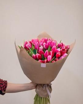 Chiuda in su a portata di mano che tiene il mazzo del fiore del tulipano