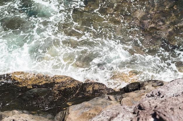 Chiuda in su acqua ondulata in spiaggia