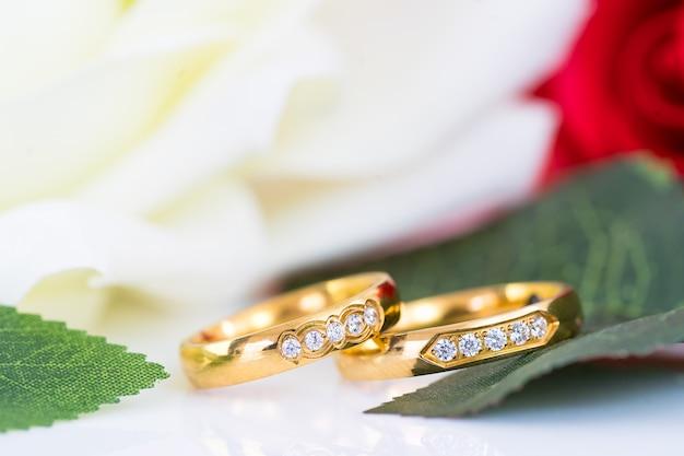 Chiuda in su degli anelli di cerimonia nuziale e della rosa rossa dell'oro