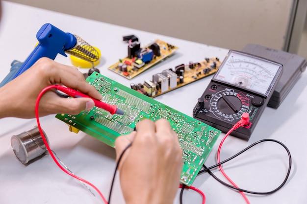 Chiuda in su degli strumenti della stretta degli uomini della mano riparano l'elettronica.