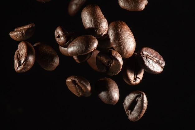 Chiuda in su dei chicchi di caffè di volo