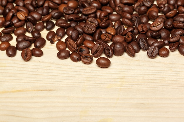 Chiuda in su dei chicchi di caffè su una priorità bassa di legno