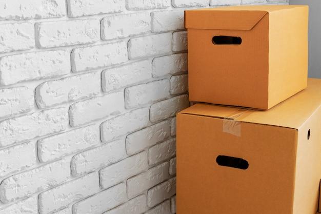 Chiuda in su dei contenitori di cartone commoventi in una stanza vuota