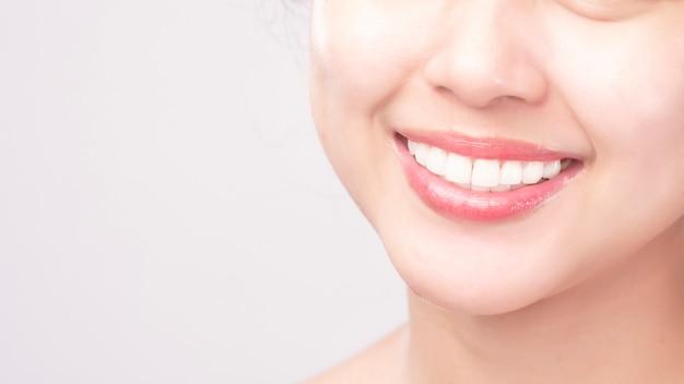 Chiuda in su dei denti sani bianchi della giovane donna di bello sorriso