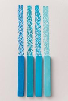 Chiuda in su dei gessi pastello pastello di colore blu sopra la sua propria traccia