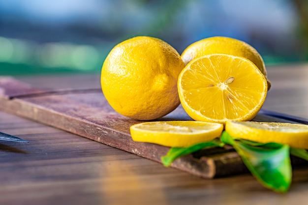 Chiuda in su dei limoni su superficie di legno