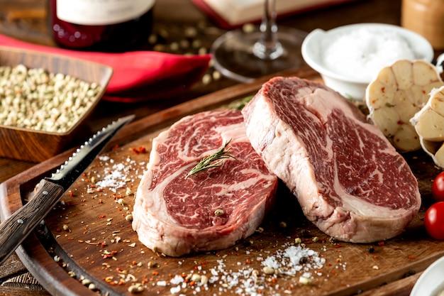 Chiuda in su dei pezzi grezzi della bistecca guarniti con sale e le erbe