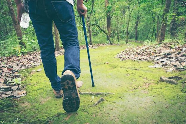 Chiuda in su dei piedi del maschio che fanno un'escursione / che arrampicano.