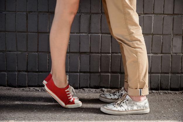 Chiuda in su dei piedini della coppia nei keds sopra la parete grigia.