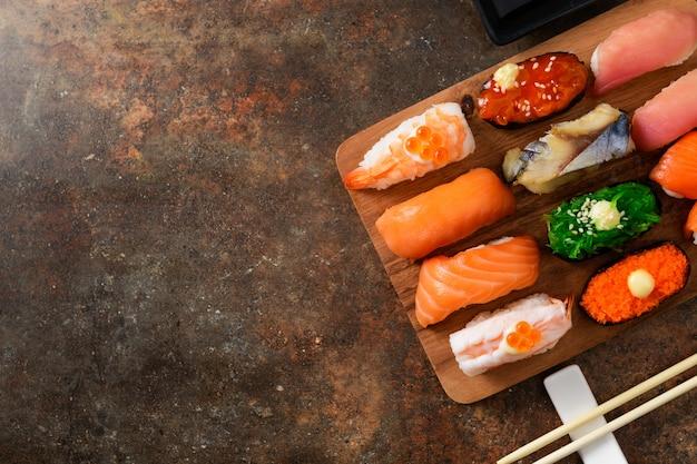 Chiuda in su dei sushi del sashimi messi con le bacchette
