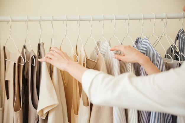 Chiuda in su dei vestiti che appendono sulla cremagliera