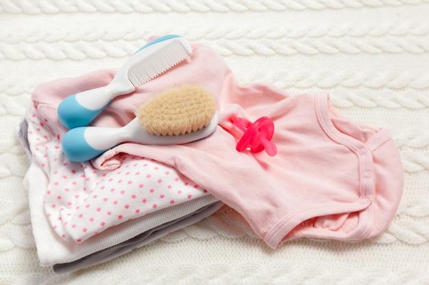 Chiuda in su dei vestiti del bambino per neonato sulla tabella