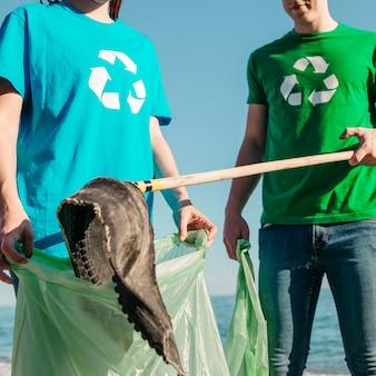 Chiuda in su dei volontari che raccolgono rifiuti in spiaggia
