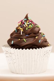 Chiuda in su del bigné del cioccolato con spruzza (verticale)