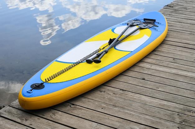 Chiuda in su del bordo gonfiabile del sup vicino al fiume. tavola sup, stand up paddle board