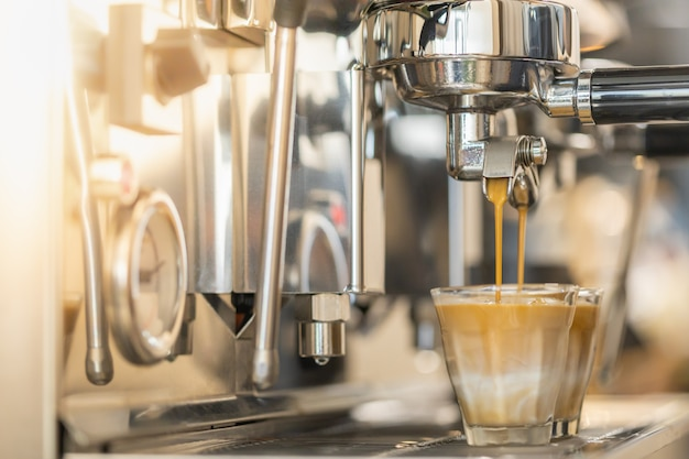 Chiuda in su del caffè espresso che versa dalla macchina da caffè automatica
