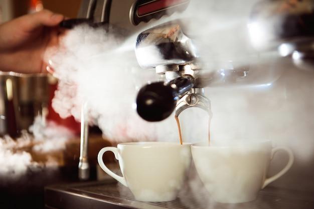 Chiuda in su del caffè espresso che versa dalla macchina del caffè in due tazze bianche. birra professionale per cappuccino