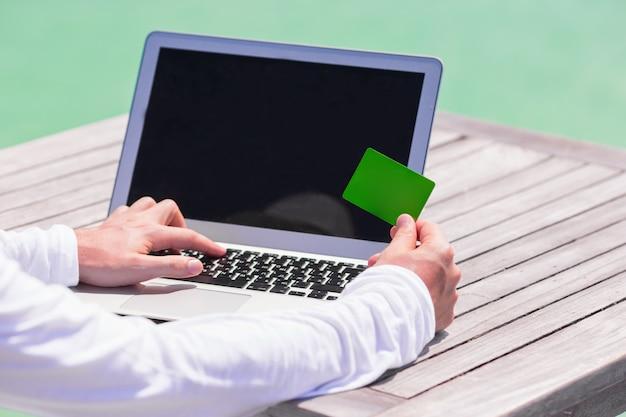 Chiuda in su del calcolatore e della carta di credito sulla tabella