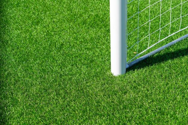 Chiuda in su del cancello di calcio di calcio con rete bianca ed erba verde