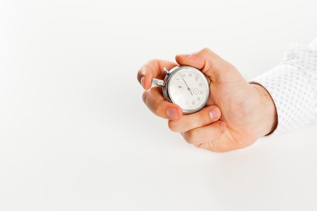 Chiuda in su del cronometro della holding della mano, isolato su superficie bianca