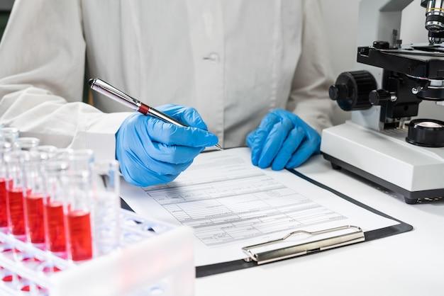 Chiuda in su del documento maschio di prescrizione di scrittura del medico
