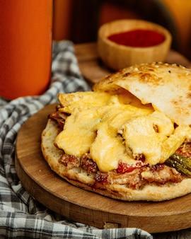 Chiuda in su del doner di pollo con patatine fritte di pomodoro formaggio fuso e cetriolo sottaceto