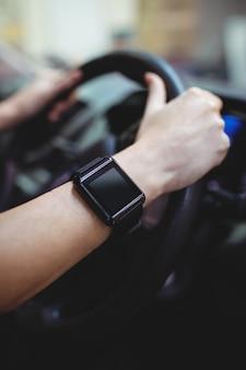 Chiuda in su del driver con l'orologio astuto in furgone