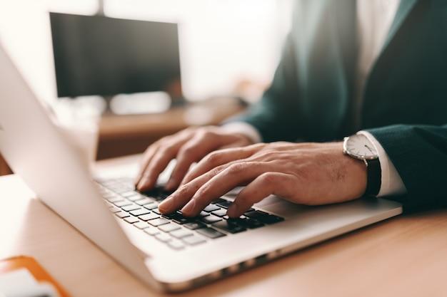 Chiuda in su del email di battitura a macchina dell'uomo sul computer portatile.