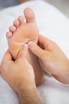 Chiuda in su del fisioterapista che dà ad un paziente un massaggio del piede