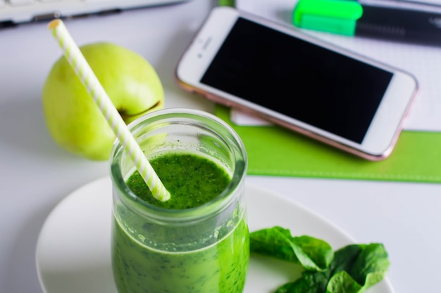 Chiuda in su del frullato verde sano sul tavolo di lavoro sul posto di lavoro con il taccuino