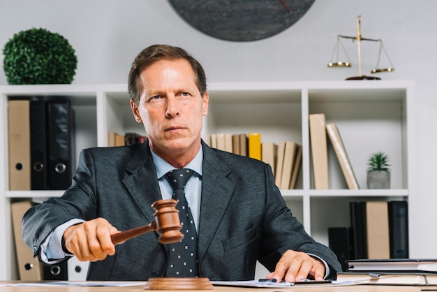 Chiuda in su del giudice maschio che colpisce il martelletto sul blocco di legno
