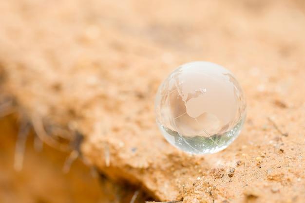 Chiuda in su del globo di cristallo che riposa sul fango.