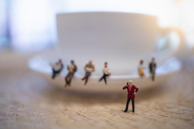 Chiuda in su del gruppo di figura miniatura dell'uomo d'affari che si leva in piedi e fa la telefonata con la tazza di caffè bianca.