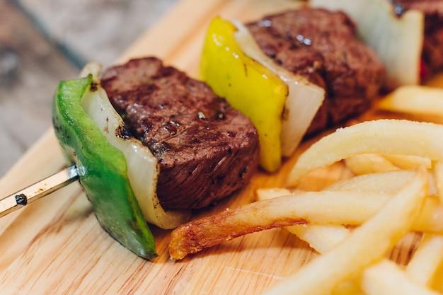 Chiuda in su del kebab del manzo del bbq servito con le patate fritte