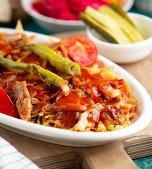 Chiuda in su del kebab turco del doner del pollo con i shoestrings e la salsa di pomodori