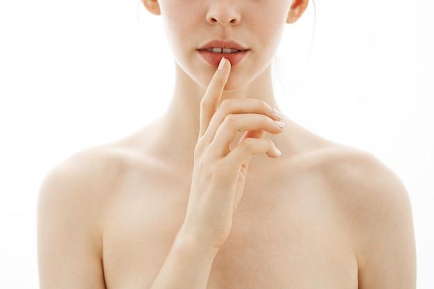 Chiuda in su del labbro commovente della giovane bella donna nuda tenera sopra priorità bassa bianca. copia spazio.