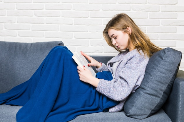 Chiuda in su del libro di lettura ragazza teenager di menzogne che si rilassa a casa