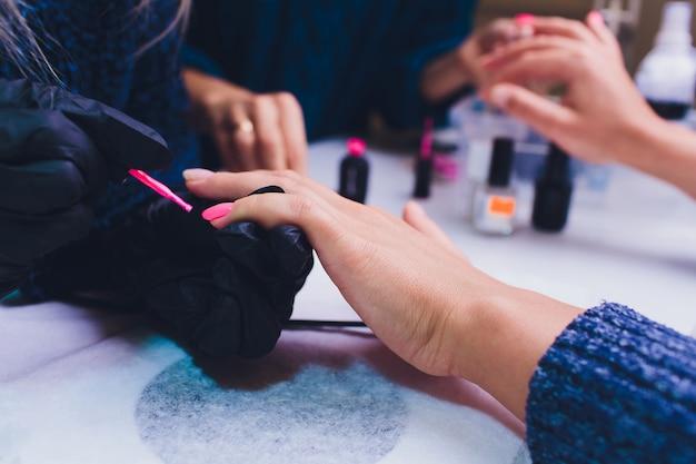 Chiuda in su del manicure trattato della francia al salone di bellezza.