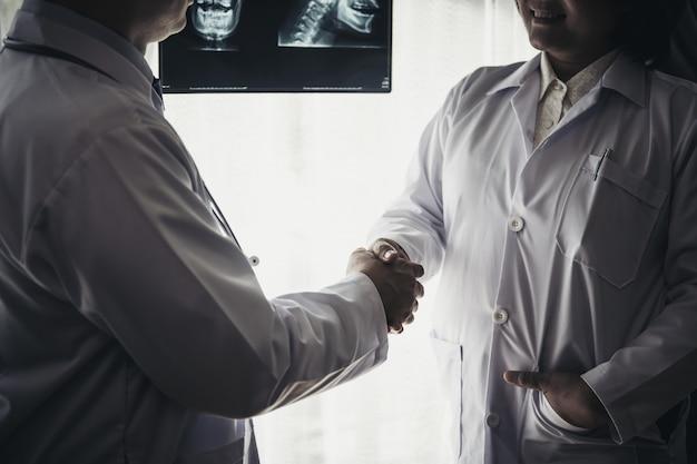 Chiuda in su del medico che dà una stretta di mano al suo partner, con successo.