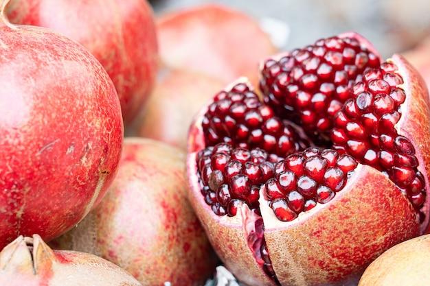 Chiuda in su del melograno fresco per l'estratto all'acqua della frutta.