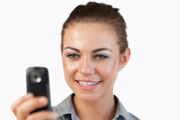 Chiuda in su del messaggio di testo sorridente della lettura della donna di affari