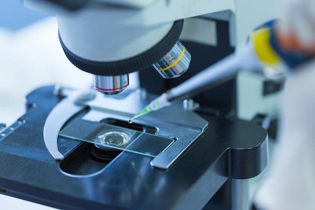 Chiuda in su del microscopio al laboratorio di sangue, concept science and technology